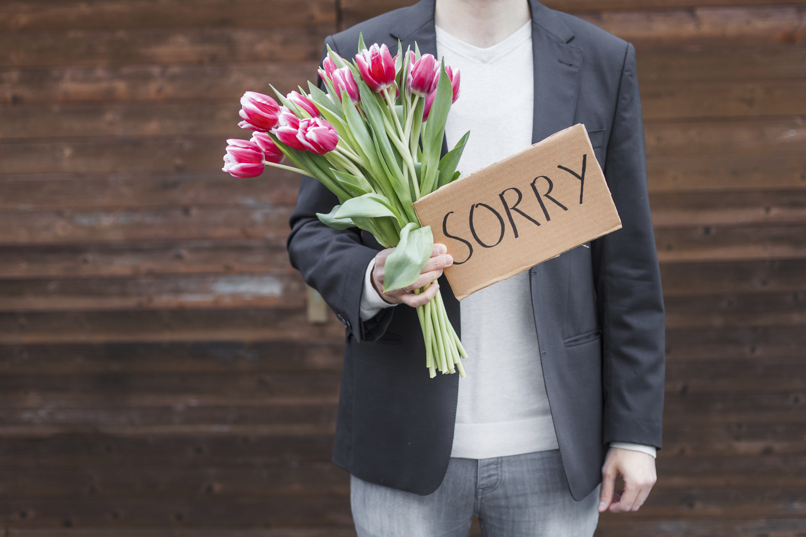 Man apologizing with flowers